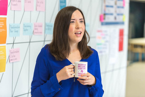 Photo of Helen Morris, Fast Streamer, standing in front of a white board covered in post it notes