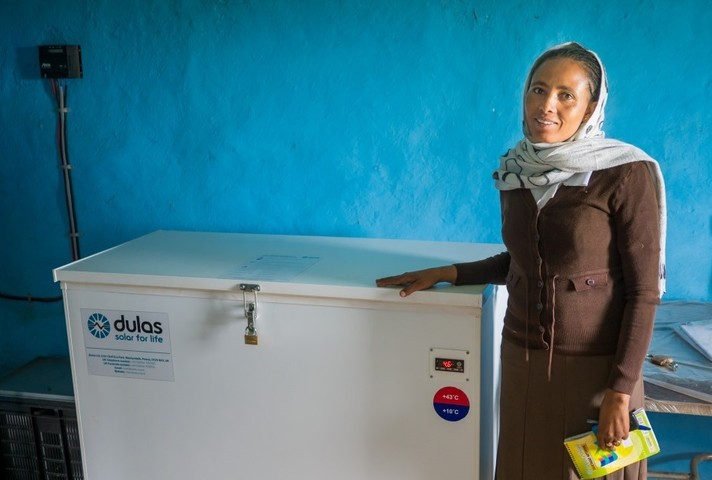 A woman stands next to a Dulas produced fridge, distributed by UK aid.