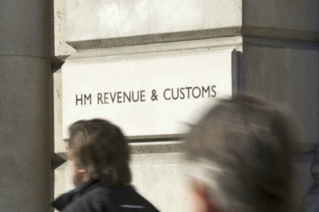 People walking past HM Revenue and Customs sign into 100 Parilament Street.