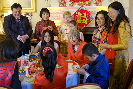 Prime Minister Theresa May sitting at table with children doing paper cutting exercise at Chinese New Year reception
