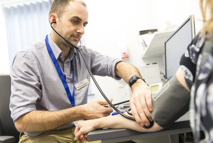 Doctor using stethoscope on patient's arm