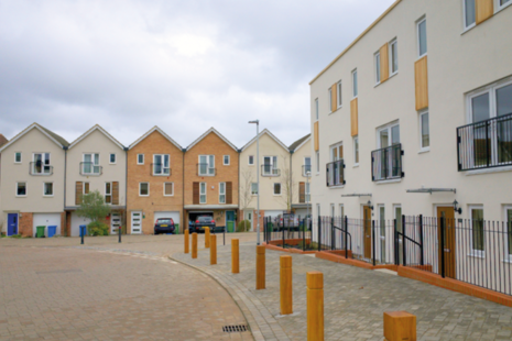 Suburban houses and flats with bollards lining the pavement.