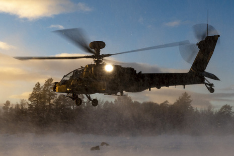 An Apache AH1D helicopter makes a landing in snowy conditions.