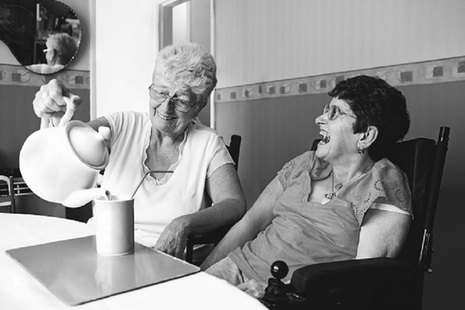 Two ladies laughing while having a cup of tea