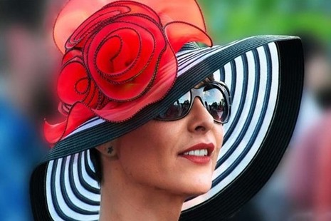 Woman wearing a large black and white striped hat with a red flower on it