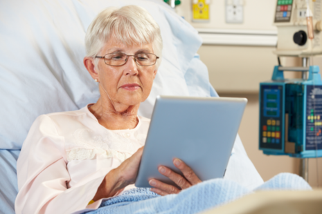 Older lady in bed using iPad in hospital