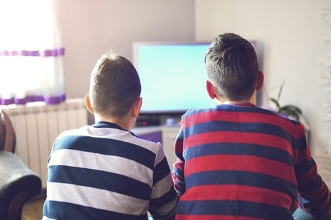 Two boys sitting in front of a television