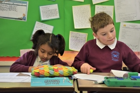 Male and female KS2 pupils writing