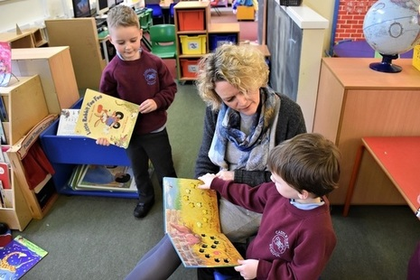 Reception pupils reading with teacher
