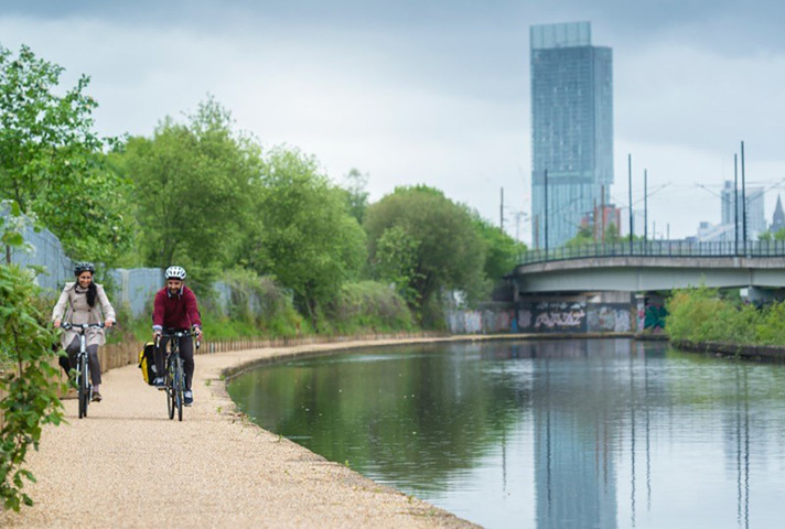 Picture of people cycling along a river.