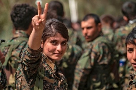 A female fighter of the US-backed Kurdish-led Syrian Democratic Forces (SDF) flashes the victory gesture while celebrating near the Omar oil field in the eastern Syrian Deir Ezzor province on March 23, 2019.