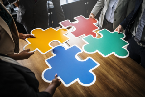People holding pieces of a jigsaw puzzle