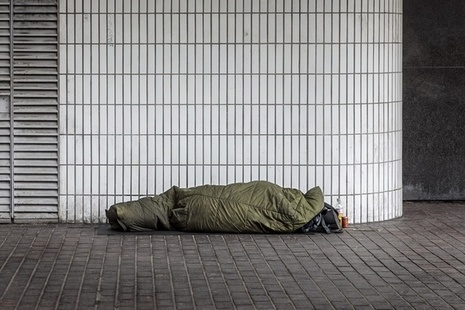A homeless person sleeping rough in a sleeping bag.