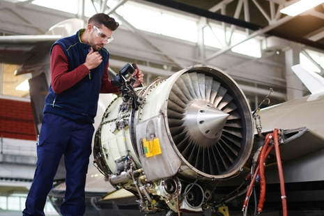 An engineer works on an aircraft turbine.