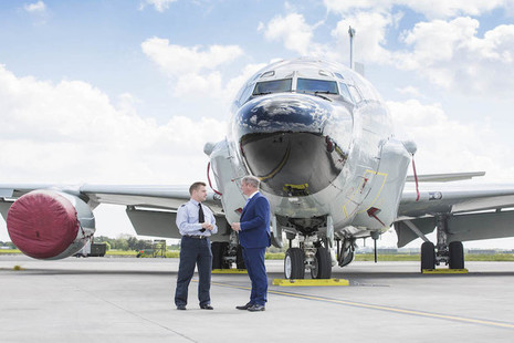 Defence Minister Stuart Andrew talking with an RAF officer in front of a miltary aircraft