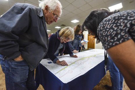 Members of the public studying a map at an engagement event