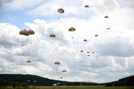 Paratroopers fly through the sky