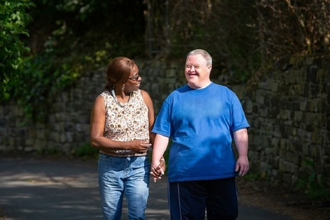 Carer and man with Down's syndrome walking down the street