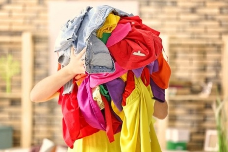Person holding a large pile of colourful clothing