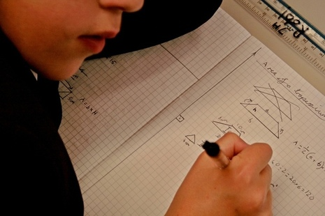 Close up of child writing in maths workbook
