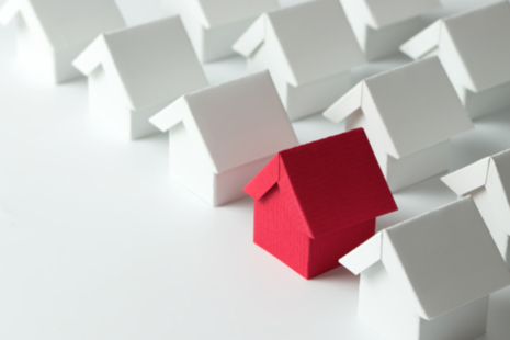 A red paper house placed alongside rows of white papers houses