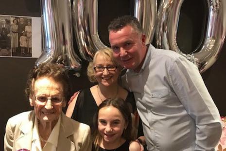 Family celebrating someones 100th birthday.