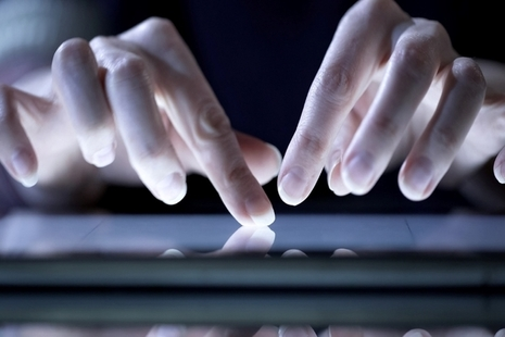 fingers using a touchpad lit up by a laptop screen