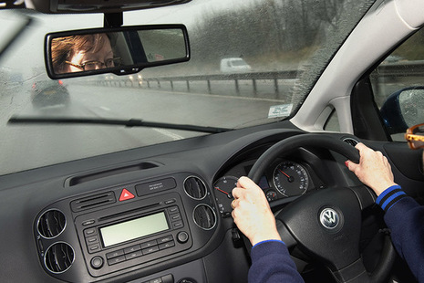 Photo of a driver, with their hands on a steering wheel