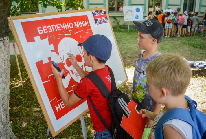 children looking at a diagram about mines in Ukraine