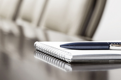 a notebook and pen on a boardroom table