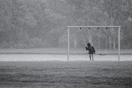 child playing outside in the rain