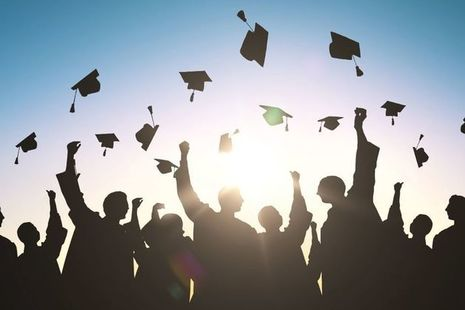 student thwowing mortarboards in air