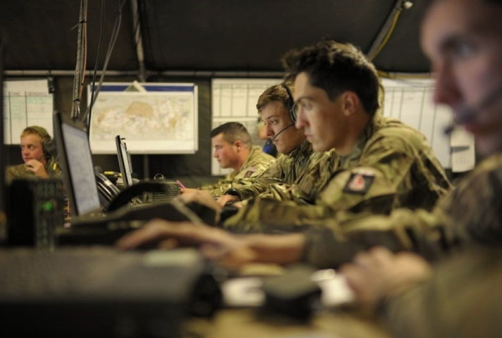 Battlegroup Headquarters with soldiers sitting at a desk some with headsets looking at computers.