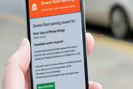 Close up of a smart phone with a flood warning on the screen for the River Goyt at Whaley Bridge