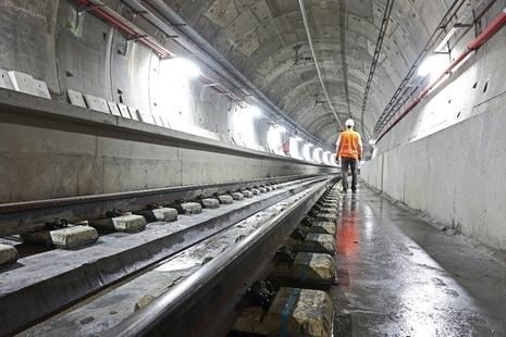 workman walking through a rail tunnel