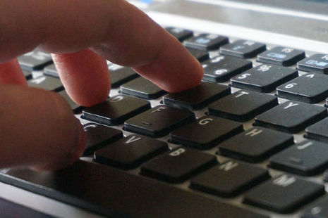Stock image of a hand typing on a laptop.
