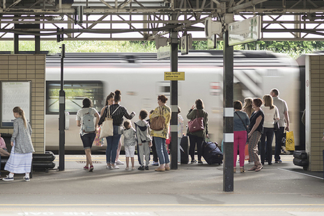 Group of rail passengers with luggage waiting on station platform as a train pulls in