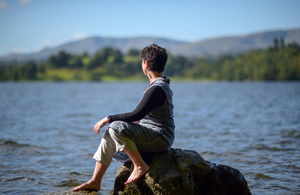 Local artist Caroline Stow sitting on a rock and looking over Windermere.