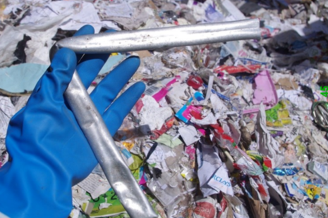 Hand in a blue glove holding a bent metal pipe with waste in the background
