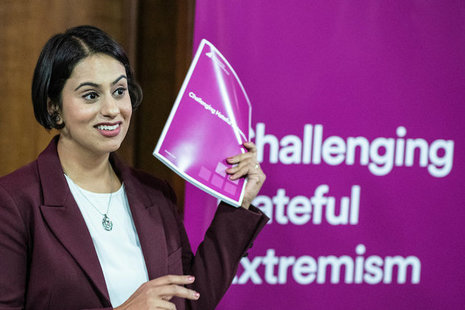 "Sara Khan holding a copy of the report ""Challenging hateful extremism"""