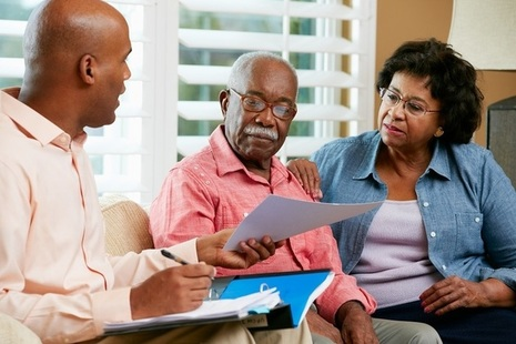 Image of eldery couple looking at paperwork with their financial adviser or younger male family member