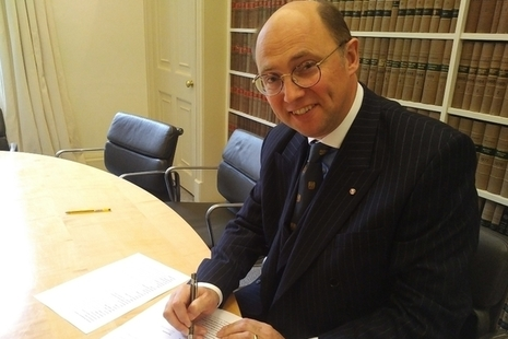 An image of Mark Watson-Gandy signing a document