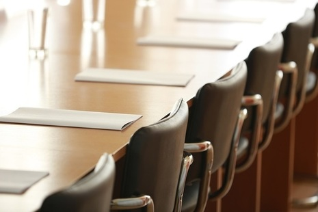 Boardroom with chairs, paper and glasses of water