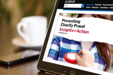 A computer screen showing the front cover of a research report about fraud in UK charities.