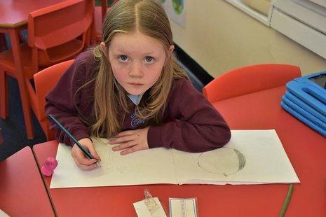 KS1 pupil writing on whiteboard