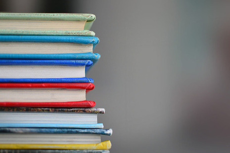 A pile of different-coloured hardback books