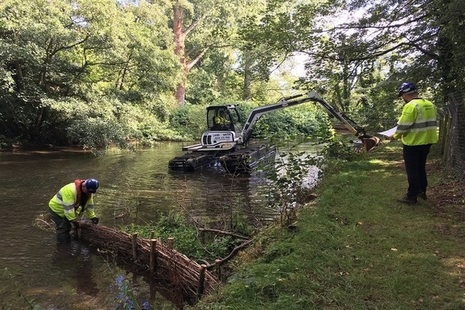 Stabilising and re-profiling river bank with an amphibious excavator.