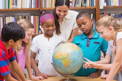 Group of children with their teacher in a library looking at a globe