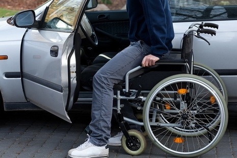 Man with wheelchair getting into car