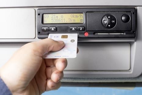 Driver inserting a digital tachograph card into a tachograph unit